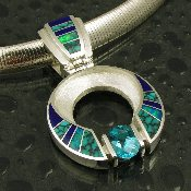 Amazing sterling silver pendant inlaid with spiderweb turquoise, deep blue lapis and genuine Australian opal by Mark Hileman. A channel set 2 carat blue topaz accents the inlaid stones.
