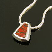 Unique inlaid dinosaur bone sterling silver pendant. The handmade silver pendant is inlaid with one piece of gem dinosaur bone with red-orange cells surrounded by black matrix.