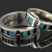 His and hers sterling silver black diamond wedding ring set inlaid with Australian opal and black onyx. Matching handmade wedding bands feature 2 round black diamonds flanked by alternating onyx and blue-green Australian opal inlay.