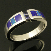 Sterling silver band featuring 2 channel set blue sapphires accented by inlaid lapis and Australian opal. The two princess cut blue sapphires have a total weight of .16 carats and are high quality. Great wedding ring!