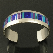 Handmade sterling silver wide cuff bracelet inlaid with lapis, sugilite, cerrulite and turquoise. Handcrafted with a nice heavy weight mounting and top quality inlay materials.