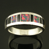 Woman's sterling silver ring inlaid with Gilson opal and black onyx. The 3 pieces of inlaid red and orange firing Gilson created opal are a striking contrast to the 4 pieces of black onyx surrounding them.