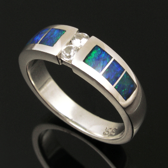 Handmade sterling silver wedding ring inlaid with Australian opal accented by white sapphires. Beautiful inlaid blue-green Australian opal surrounds two round brilliant cut white sapphires in this unique wedding band.