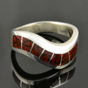 Dinosaur bone sterling silver inlay ring featuring 7 pieces of red orange dinosaur bone inlaid in a unique curved channel ladies ring design. The gem dinosaur bone inlay in this ring is reddish orange with black webbing or matrix.