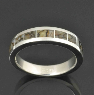 Dinosaur bone wedding ring handcrafted in sterling silver by Hileman Silver Jewelry. 7 pieces of gray dinosaur bone are inlaid in this unique bone wedding ring.